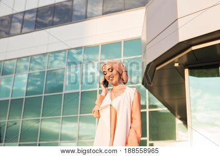 happy islamic woman using smart phone outdoors