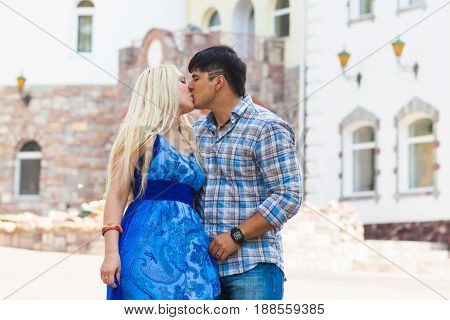 Pretty summer sunny outdoor portrait of young stylish couple while kissing on the street.