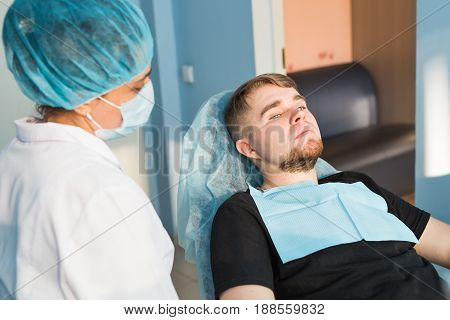 Portrait of male. smile face. Dental care Concept. Dental inspection is being given to beautiful man surrounded by dentist.