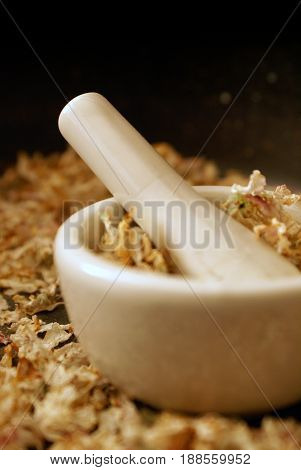 A vertical orientation of a mortar and pestle ready for preparing some dried Apple Blossoms into herbals for medical uses.