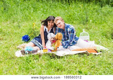 Happy family at picnic on the summer meadow.