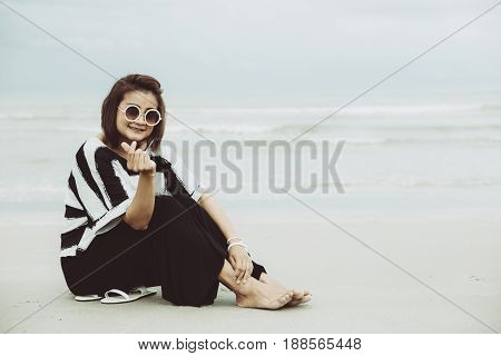 Portrait Asian Single Hipster Indy Women Wear Sunglasses Siting On The Beach Happy With Hand Finger