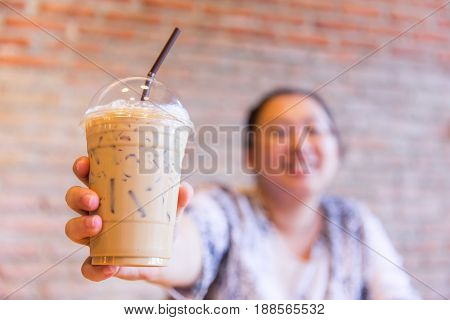 fatty asian women smile with ice cool milk coffee drink in summer season.
