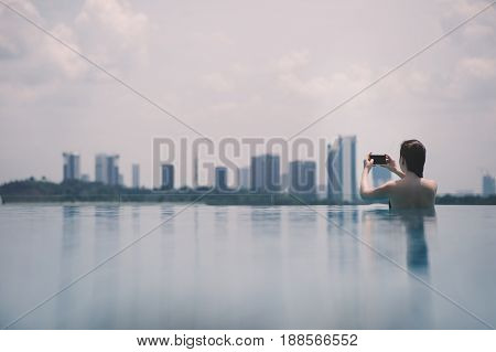 Beautiful girl in the pool with mobile phone on the background of the city of Malaysia Putrajaya. Putrajaya Skyscrapers