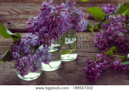 Lilac Flowers In Jars On The Old Wooden Background