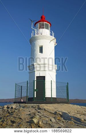 a lighthouse stands on a raised platform in the middle of the sea. Lighthouse in the sunshine