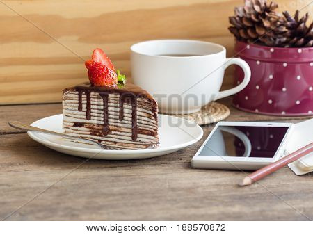 Homemade chocolate crepe cake or mille crepe cake topping with strawberry and dark chocolate sauce, Chocolate cake on white plate. Crepe cake chocolate sauce so delicious bitter and sweet. Homemade chocolate cake on rustic wood table serve with tea or cof