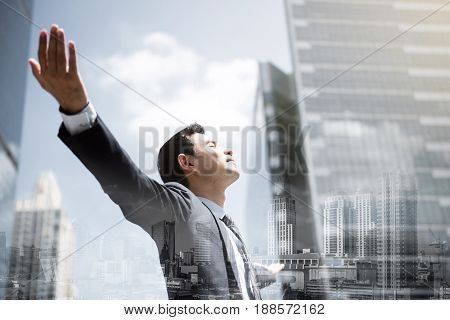 Businessman in the city raising his arms open palms with face looking up - empowering success and freedom concepts double exposure effect