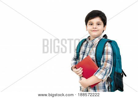 Cute Asian boy carrying school bag and holding book in hands isolated on white background with copy space - back to school and education concepts