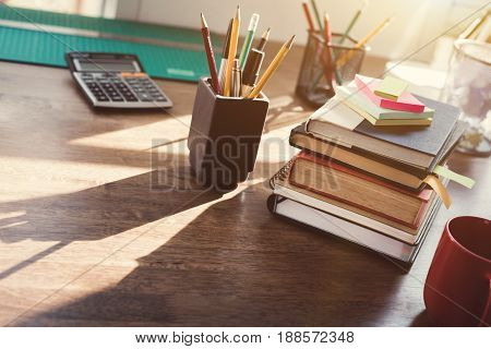 Stack of books and stationery on the desk - vintage tone effect