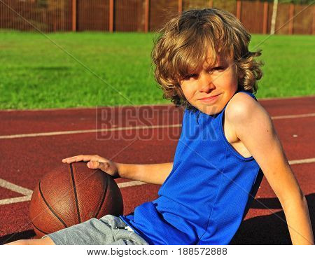 Shaggy boy on the court with basketball summer outdoor scene