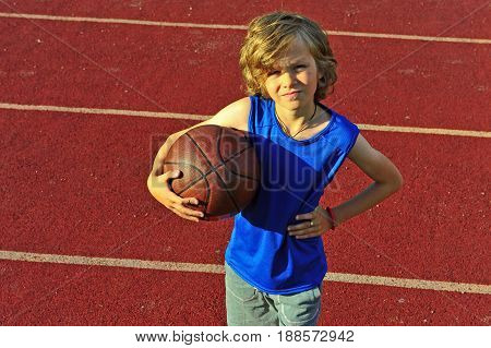 Portrait of a kid with a basketball on the court