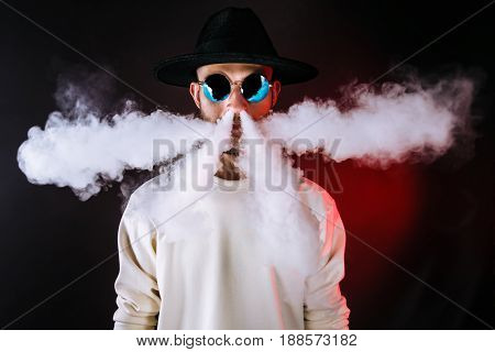 Stylish man in sunglasses puffing the vapor on the black background.