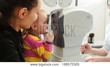 Dark-haired Mother and young daughter came for a consultation with the optometrist