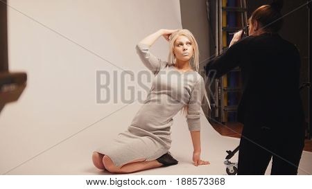 Blonde girl in grey dress posing for the photographer in the photo Studio