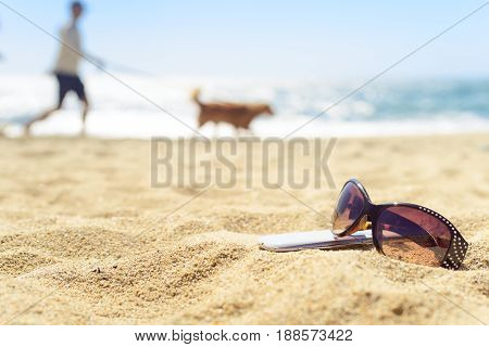Close up sunglasses and phone on the beach with blurred silhoutte on background walking with dog.
