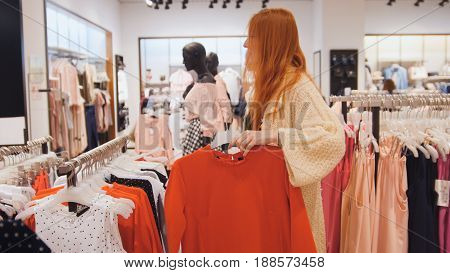 Shopping for woman. Young woman holding a hanger with a red dress