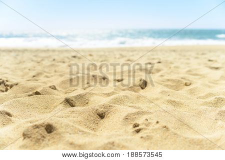 Close up of warm yellow sand on the beach, with blue luring water sparkling on background