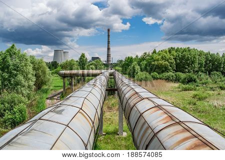 Hot water and central heating pipelines with a cogeneration plant on the background