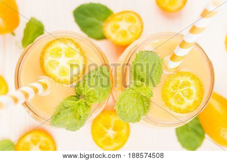 Freshly blended orange citrus kumquat fruit smoothie in glass jars with straw mint leaf cute ripe berry top view close up. White wooden board background.