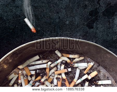 burning cigarette throwing in ashtray on dark background. world no tobacco day on may 31