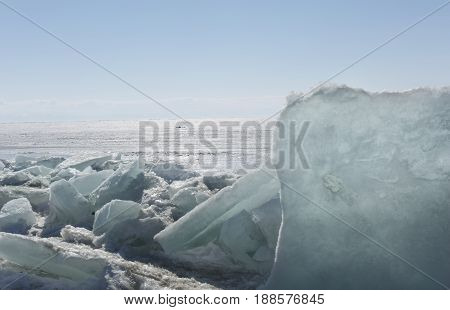 Transparent blue ice hummocks on lake Baikal shore. Siberia winter landscape view. Snow-covered ice of the lake. Big cracks in the ice floe
