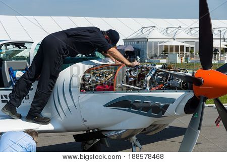 BERLIN GERMANY - MAY 21 2014: Technician inspects turboprop engine two-seater training and aerobatic low-wing aircraft Grob G 120TP. Exhibition ILA Berlin Air Show 2014