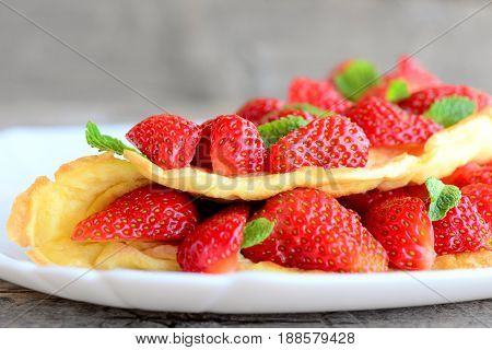 Delicious berry omelette. Omelette stuffed with juicy strawberries filling and garnished with mint leaves on a plate and a wooden table. Healthy breakfast or brunch menu. Rustic stile. Closeup