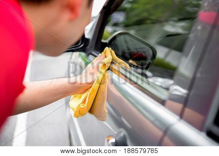 A man cleaning car with microfiber cloth - auto detailing and valeting concept