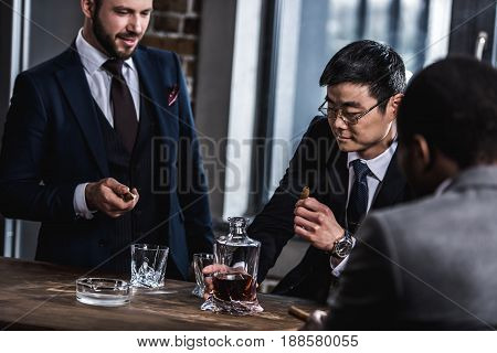 Multicultural Business Team Spending Time, Smoking Cigars And Drinking Whiskey