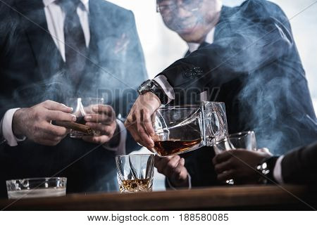 cropped view of business team spending time smoking cigars and drinking whiskey