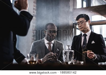 multicultural business team spending time smoking cigars and drinking whiskey