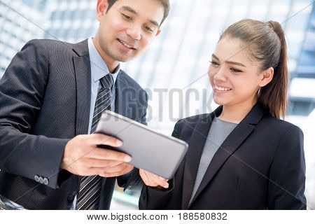 Businesswoman and businessman looking at tablet pc discussing work