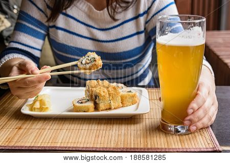 Close up of young beautiful woman holding chopsticks and glass of beer in Japanese restaurant