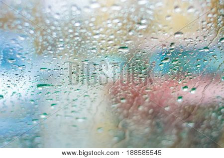 Blurry cars silhouettes through windscreen covered in raindrops