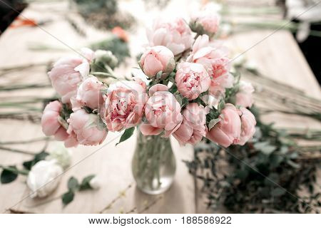 Pink peonies in vase on wooden floor and bokeh background - retro styled photo.
