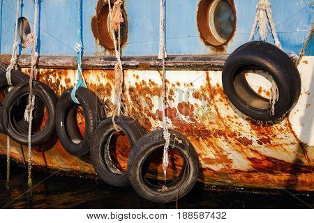 Nesebar Bulgaria - September 10 2014: Old tires on ship. Used for impact protection of a ship. Old ship in the port of the old town of Nessebar Bulgaria. Selective focus.