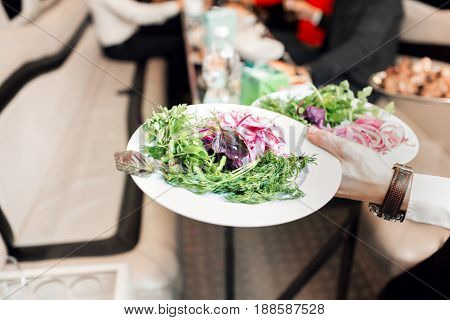 vegetables and salad close up. Waitress bringing food at the table.