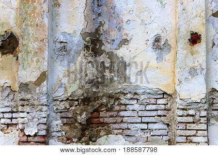 Old brick wall with which plaster and painting has partially flown. On the right and at the left on her columns from the same brick.