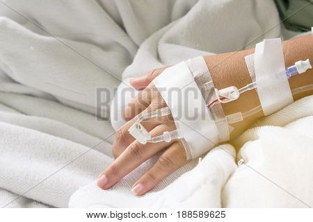 Asian woman patient hand on IV drip with saline solution fluid replacement therapy