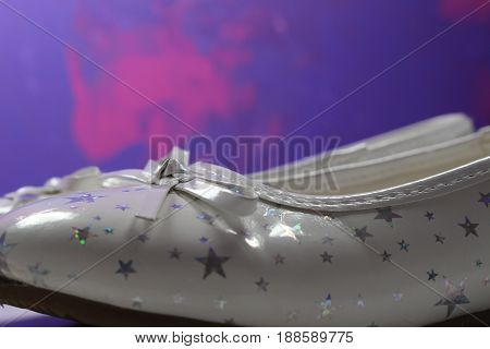 White shoes with glittering silver stars and ribbon for small girl.