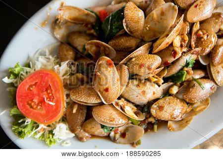 spicy fried clams with basil in the dish.