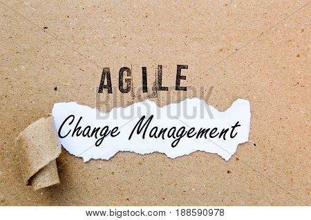 Agile Change Management - printed text underneath torn brown paper with Agile printed in ink