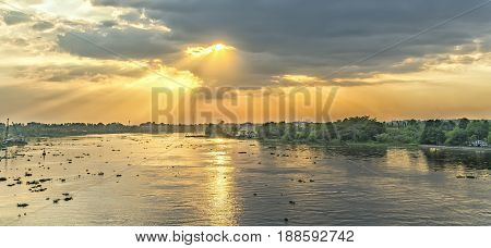 Sunset on the river in rural homeland with sun rays shining down beautifully and mysterious