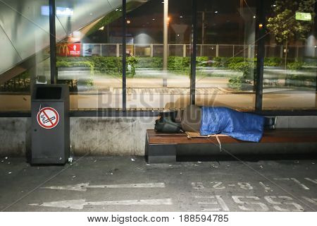 MUNICH GERMANY - MAY 6 2017 : A homeless person sleeping on a bench at the Central Bus Station at night in Munich Germany.
