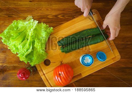 Woman slicing cucumber for salad on wooden board. Top view