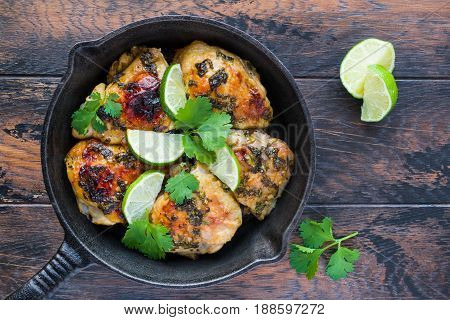 Homemade crispy cilantro lime chicken in a black cast-iron skillet on the rustic wooden table top view.