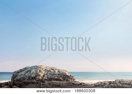 Giant rock and sea waves with blue sky at sunny day