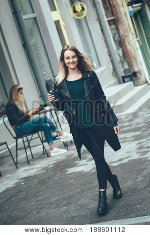 Beautiful young stylish casual woman wear in black fashion clothes walking and holding black cup of coffee, enjoying, smiling and look at cam. Lifestyle, fashion, street style concept.