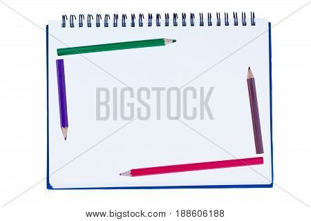 blank notebook with metal spiral and five crayons in the border of the book isolated on white background